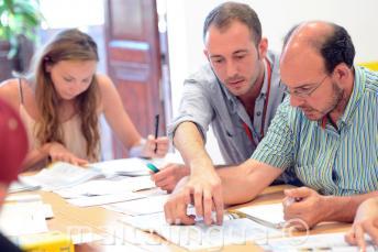 Un profesor de inglés explicando algo a un estudiante en clase