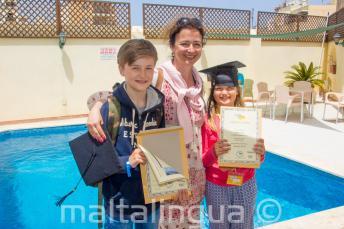 Una madre con sus dos hijos habiendo completado el curso de lengua inglesa
