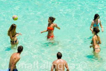 Jóvenes estudiantes jugando al volleyball en Blue Lagoon, Malta