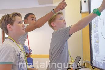 A teacher helping 2 students at an interactive whiteboard
