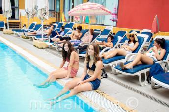 2 estudiantes con las piernas en la piscina de la residencia para jóvenes
