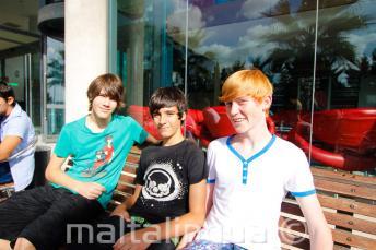 3 estudiantes sentados en un banco fuera de la residencia de la escuela