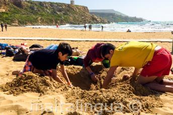 Jefe de grupo y estudiantes cavando un hoyo en la playa