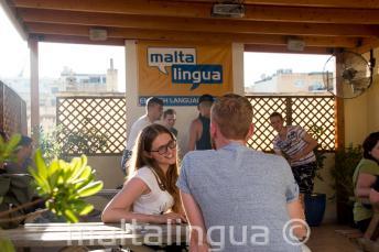 Estudiante hablando con su profesor de inglés en la terraza