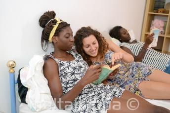 Un estudiante leyendo un libro con un miembro de la familia de acogida