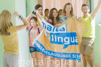 Un grupo de estudiantes sujetando una bandera en la escuela de verano
