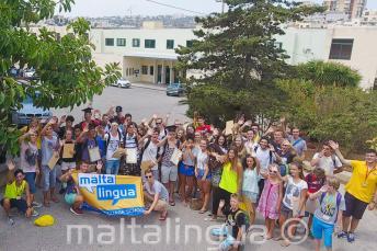Un grupo grande de jóvenes estudiantes haciendo la ola fuera de la escuela
