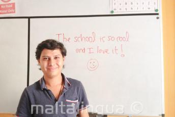 Un estudiante tras escribir una opinión positiva de la escuela en la pizarra