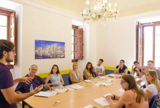 Un profesor hablando en una clase llena de estudiantes de inglés