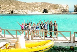 Un grupo de estudiantes cerca del barco en Blue Lagoon, Comino