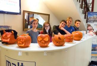 Jóvenes estudiantes con calabazas talladas en la recepción