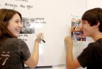 2 estudiantes trabajando juntos en la pizarra