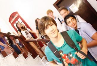 Un grupo de estudiantes en frente de una cabina roja de teléfono