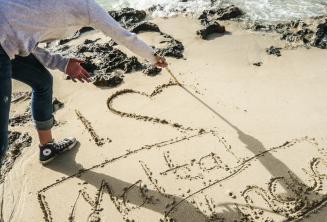 """Un estudiante escribiendo """"I LOVE"""" Maltalingua en la arena"""