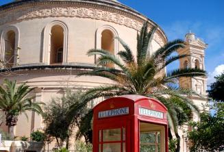 Una cabina de teléfono roja en frente de la rotonda de Mosta