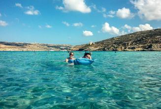 Estudiantes de la escuela de inglés nadando en la Laguna Azul en Comino