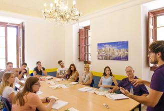 Estudiantes escuchando al profesor en clase de lengua inglesa